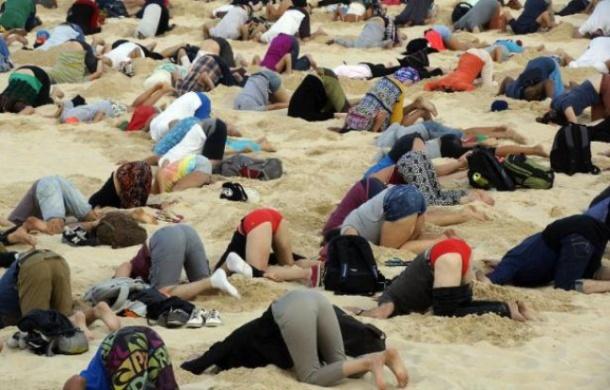 Photo publiée par le site 350.org le 13 novembre 2014 montrant des Australiens la tête dans le sable sur une célèbre plage de Sydney pour alerter le Premier ministre australien Tony Abbott des dangers du changement climatique - Tim Cole